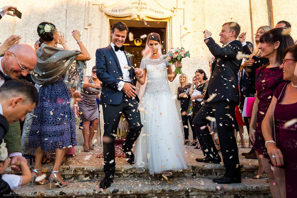 Newlyweds leave the church under a shower of confetti. Photo by Elliot Nichol Photography.