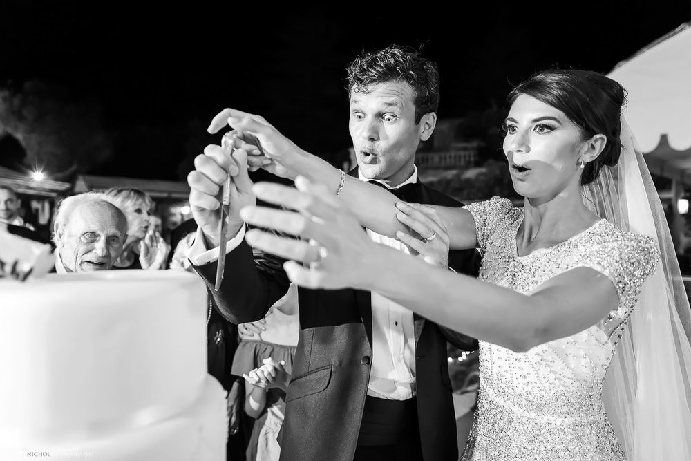 Bride and Groom's reaction to their cake topper falling off their wedding cake. Photo by wedding photojournalist Elliot Nichol.