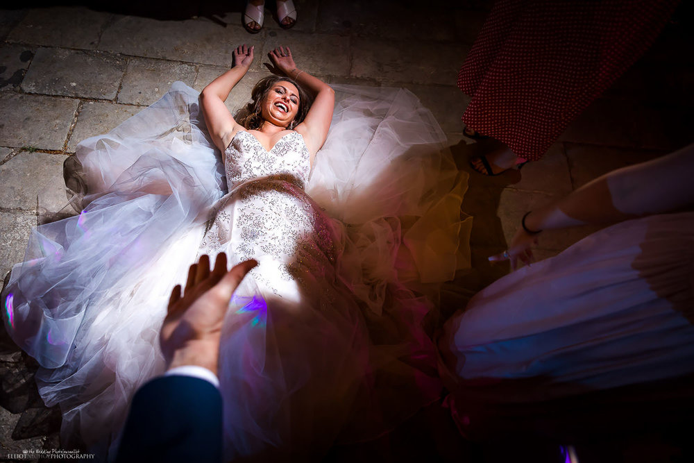 Laughing Bride after tripping up while partying at her wedding reception. Photo by Elliot Nichol Photography.