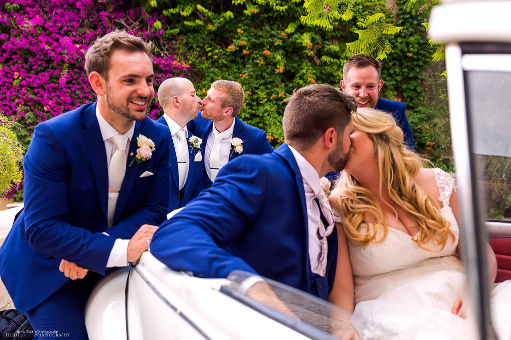 Groomsmen pretending to kiss each other during a photo of the bride and groom kissing. Photo by wedding photographer Elliot Nichol.