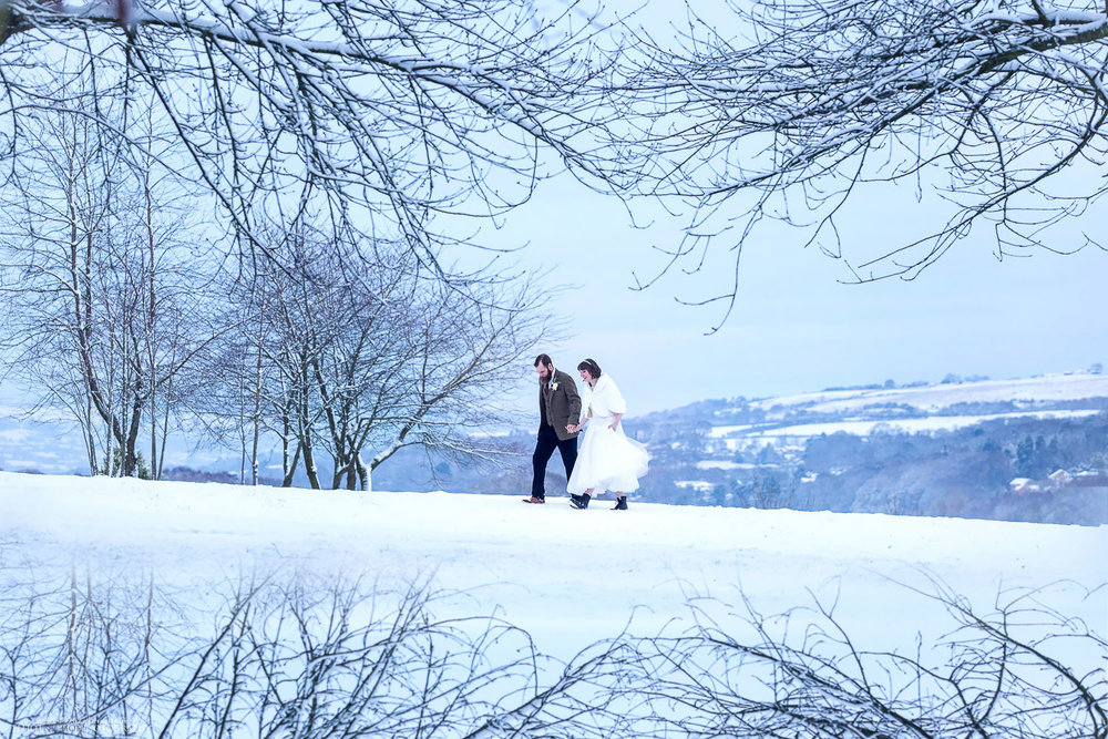 Bride and groom walking through a snow covered countryside of Northumberland on the day of their white winter wedding. Photo by Northeast wedding photographer Elliot Nichol.