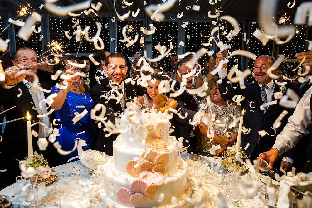 Couple cut into their wedding cake under a explosion of confetti. Photo by Northeast wedding photojournalist Elliot Nichol.