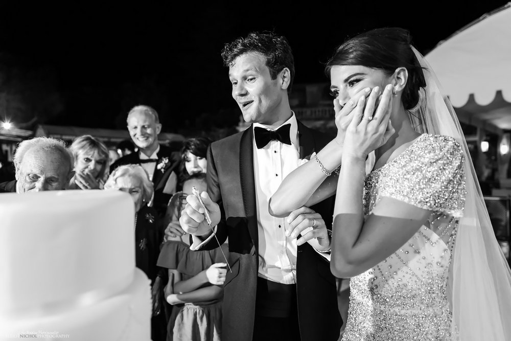 Brides reaction to their wedding cake topper falling off their wedding cake during their wedding reception. Photo by Elliot Nichol Photography.