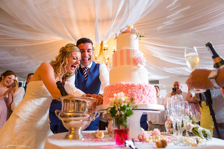 21ef649786ec Newlyweds enjoying cutting their wedding cake during their wedding  reception. This photo was used by