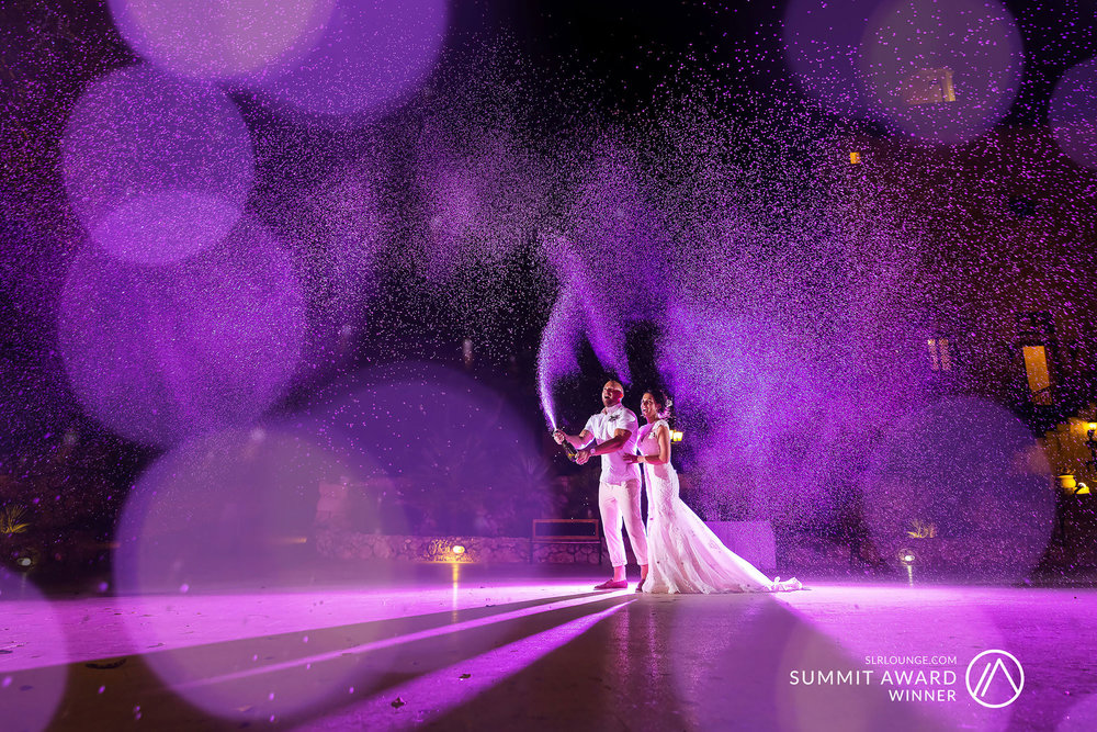 SLR Lounge's Summit Award winning image. Newlyweds have fun spraying champagne in a celebration of their marriage at their wedding reception venue. Photo by Elliot Nichol Photography. Based in the North East of England, photographing wedding throughout the UK.