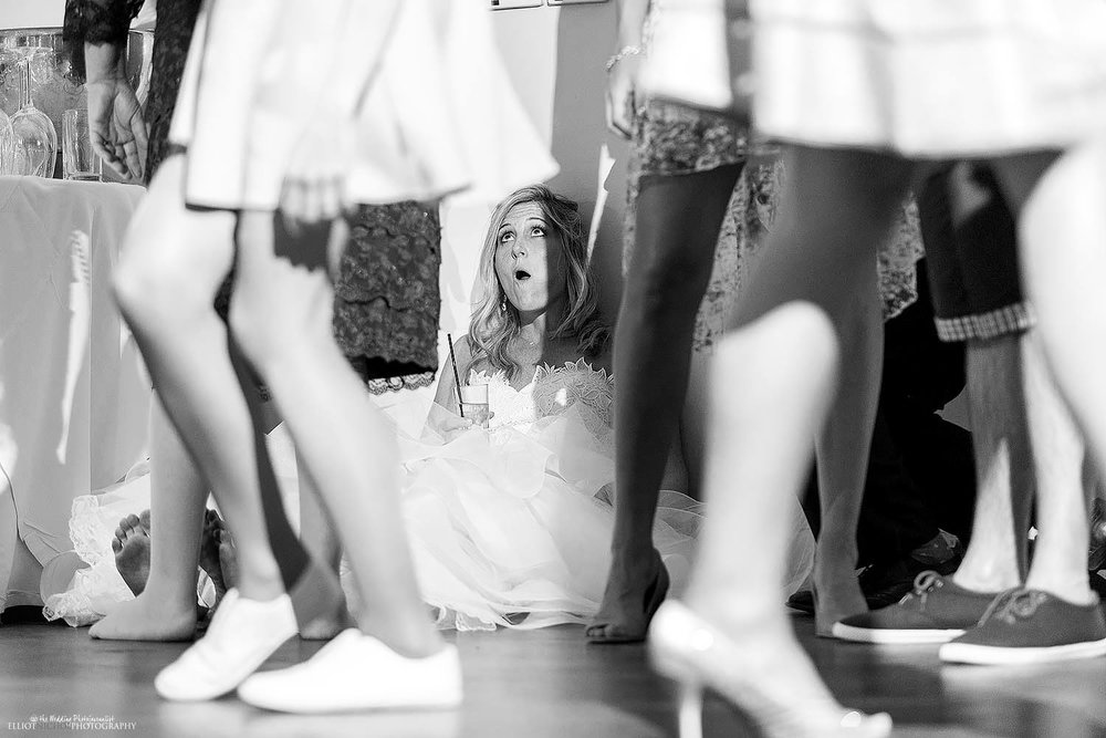 Exhausted bride sitting on the dance floor. Photo by wedding photojournalist Elliot Nichol.