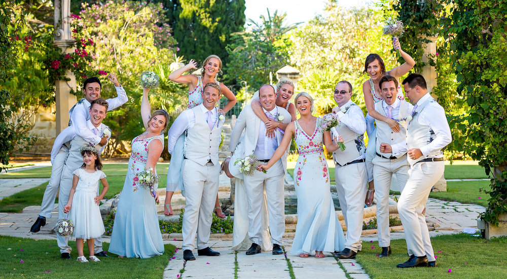 Relaxed informal wedding day wedding party group shot in the gardens of the wedding reception venue. Photo by North East of UK photographer Elliot Nichol.