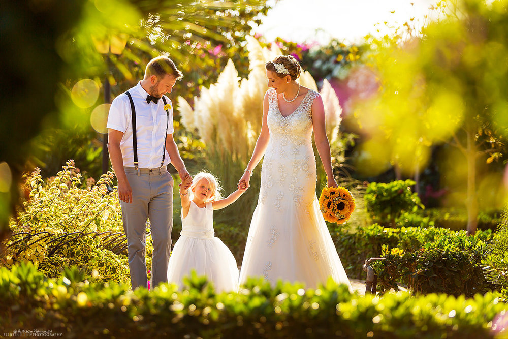 Newlyweds walk through the gardens of their wedding venue together with their young daughter. Photo by Elliot Nichol Photography.