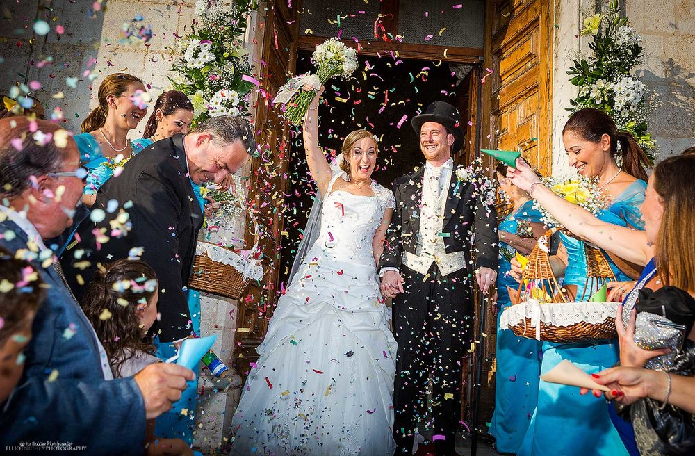 Bride and Groom exit the church under a show of colourful confetti. Photo by Elliot Nichol Photography, based in the North East of England.