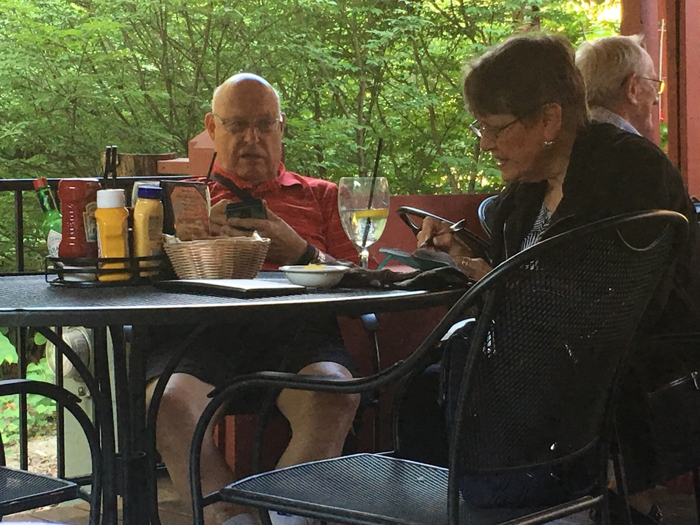 A couple dining.  He was reading and I believe she was calculating the tip.