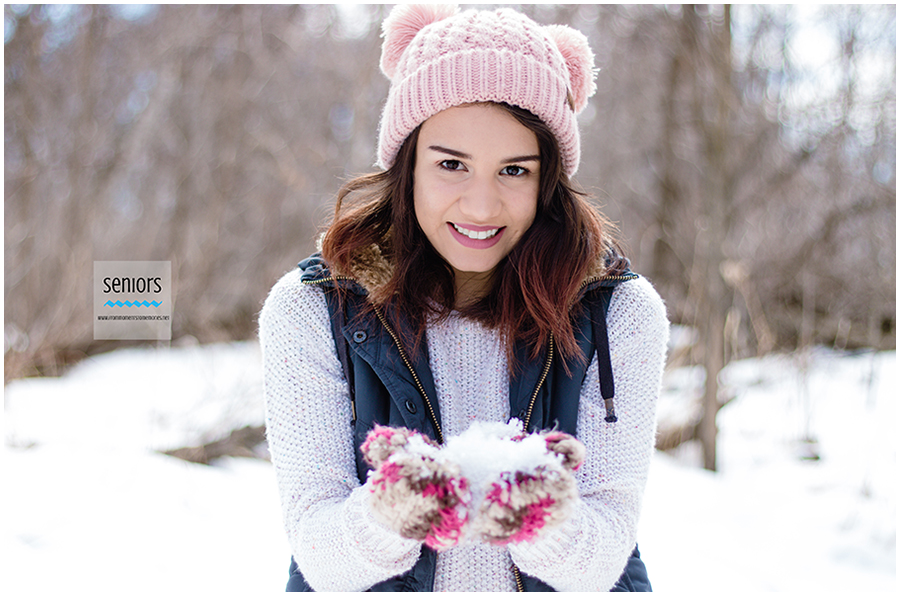 teenaged girl with hat and jacket on in winter with snow for senior pictures at woodland trails park in elk river, minnesota