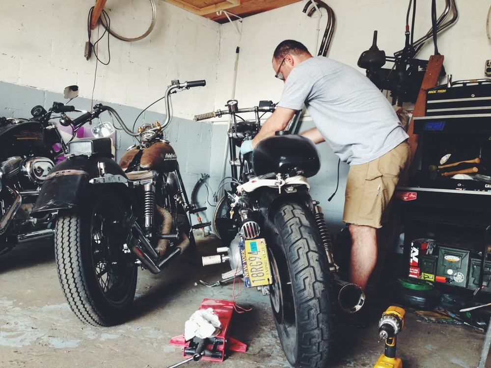 My friend Francis wrenching on his Sportster. He's changed it up three times since I've know him, swears this is the final evolution.