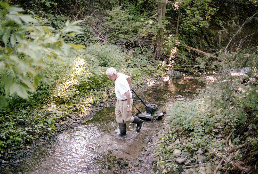 My 82 year old uncle Frank up at around 7 a.m. outside of his house in Dewitt New York. He's dragging his lawn mower across a creek so he can take care of the grass on the other side. His discipline, energy and work ethic have always inspired me.