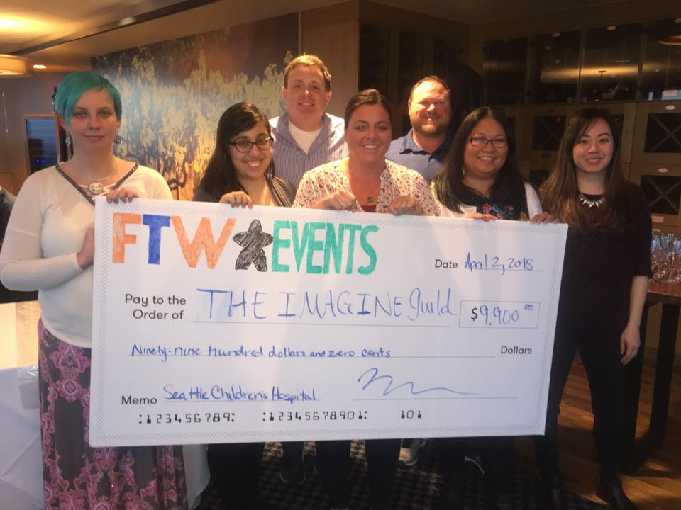 FTW Events' officers and volunteers present a check to Danny and Jennifer Kramer from the Imagine Guild.