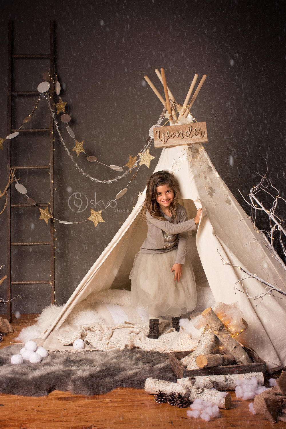 Girl stepping out of tent in a Restoration Hardware style winter mini-session photography set with stars and snow