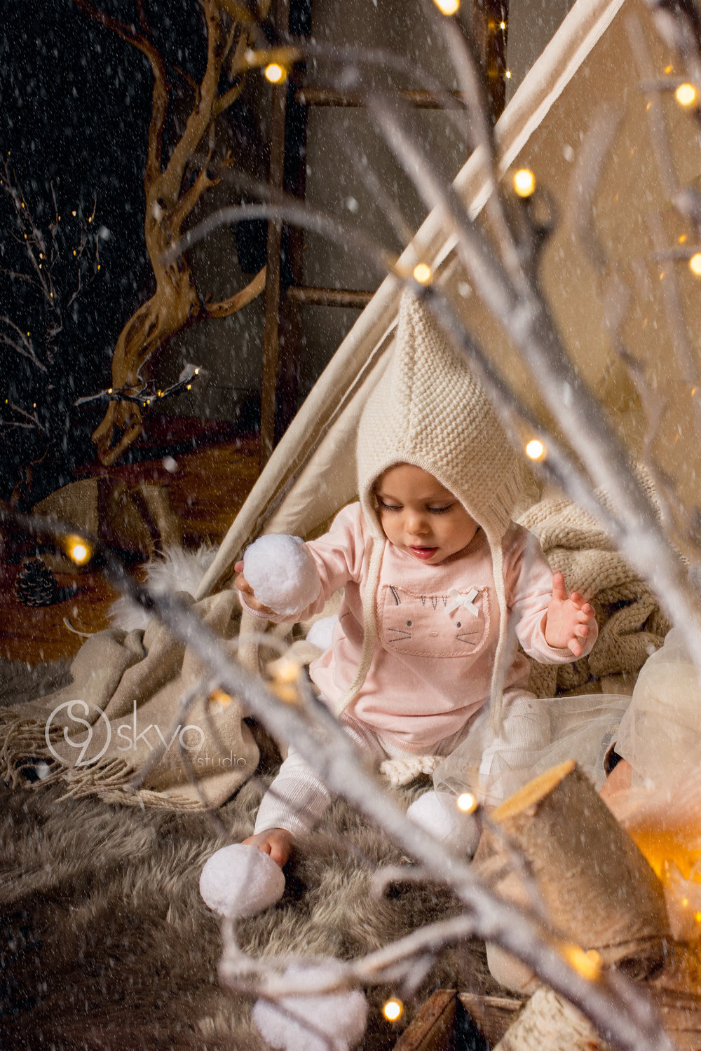 Winter mini-session with baby wearing Hanna Andersson hat and holding a snowball behind twinkle lights