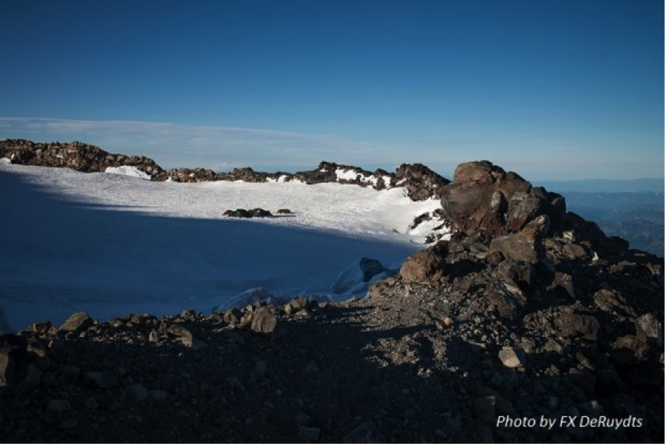 Rainier's East Crater is a 'trapped' ice plug - the crater contains the glacier. This view from near summit shows base camp in the distance.