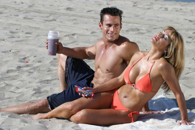 happy muscular fit couple on the beach