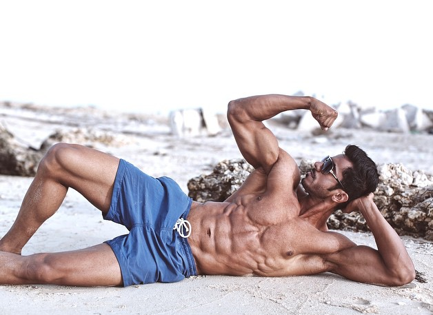 muscular model flexing on the beach