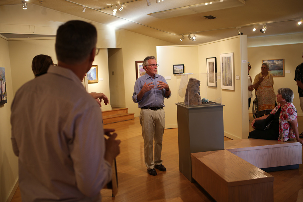 John Robinson, curator, explains setting up the display in the Kings County Art Center.