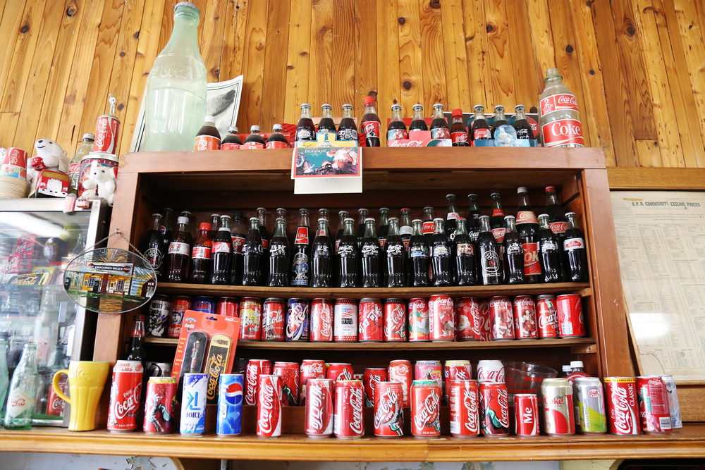 The soda shop boasts an impressive display of Coke bottles from years past.