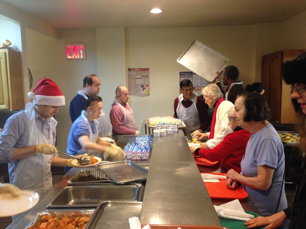 Fellow volunteers serving a holiday-themed meal at the senior center.