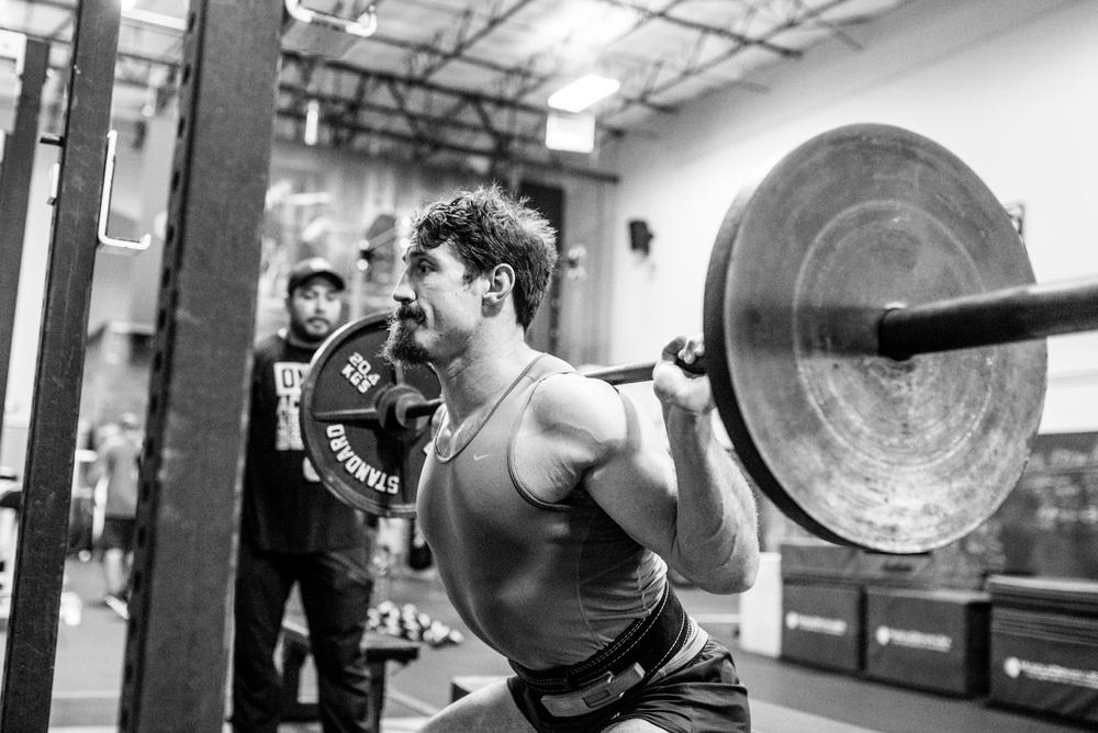 Tim squats under the supervision of his trainer Juan Leija.