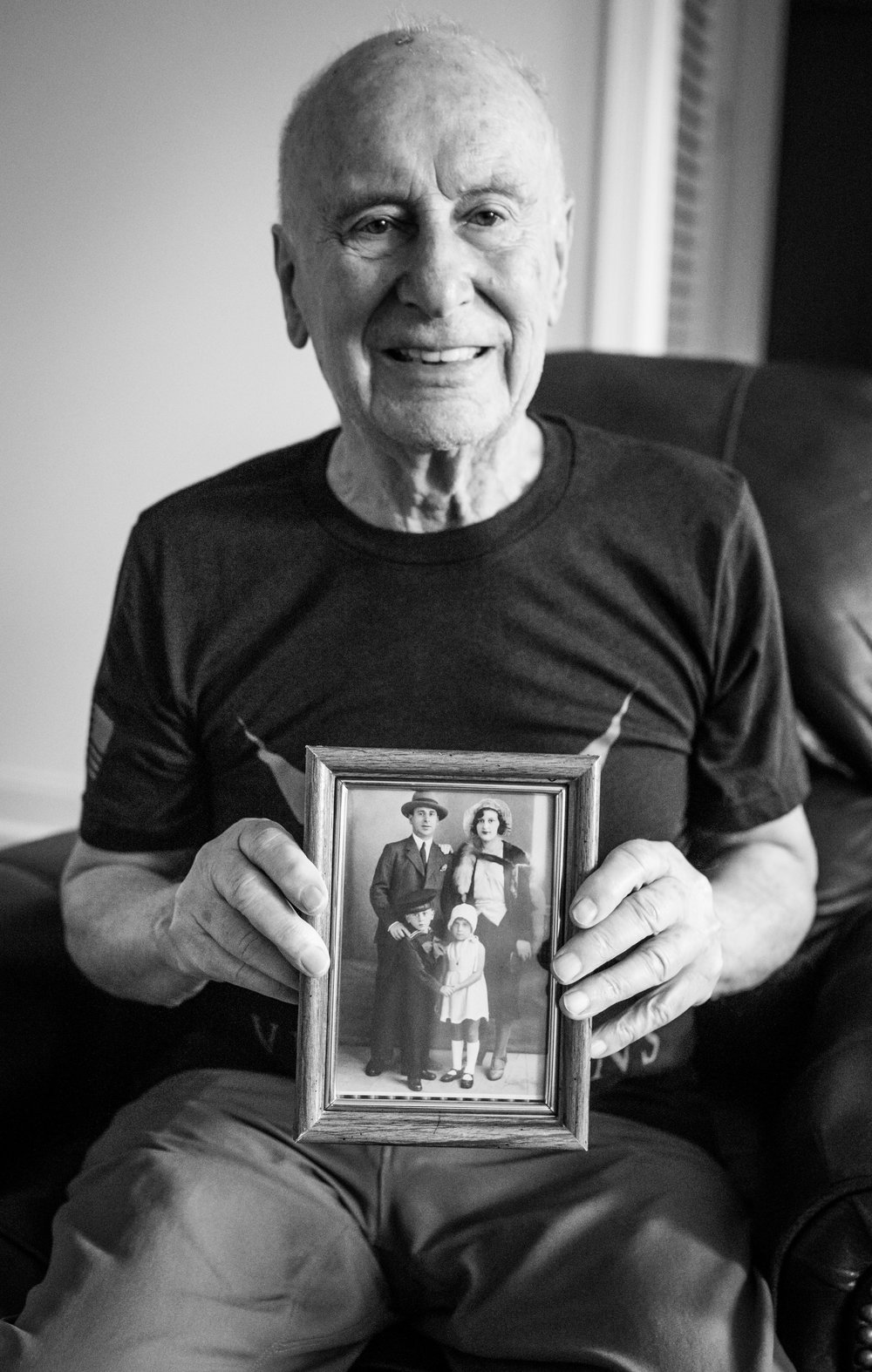 John holds a photograph of his family.  This was shortly before his mother passed away.