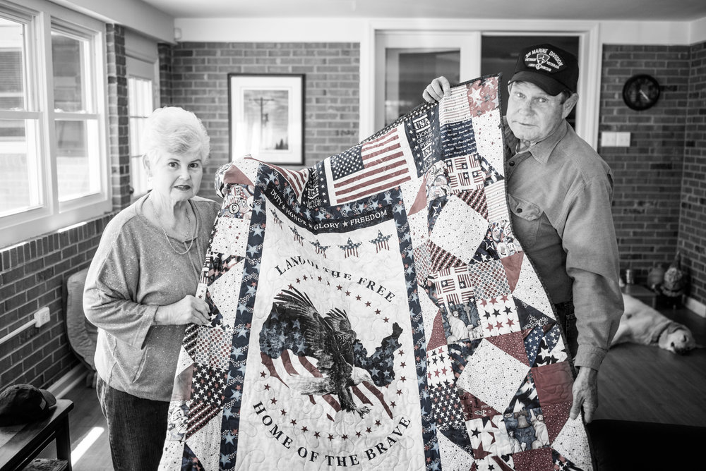 "Bobby and his wife hold up his ""Quilt of Valor."""