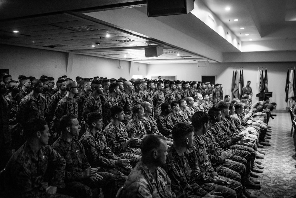 Marines, Navy Corpsmen, and Soldiers listen in as Woody speaks about his life.