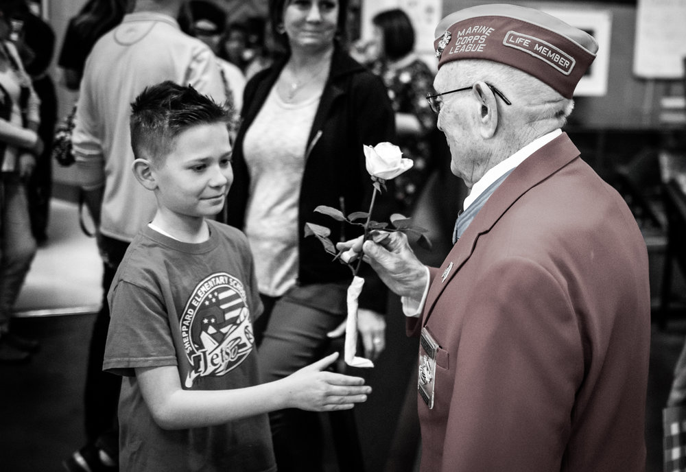 A student from Sheppard Elementary School hands Woody a white rose, a universal symbol for honor and respect.