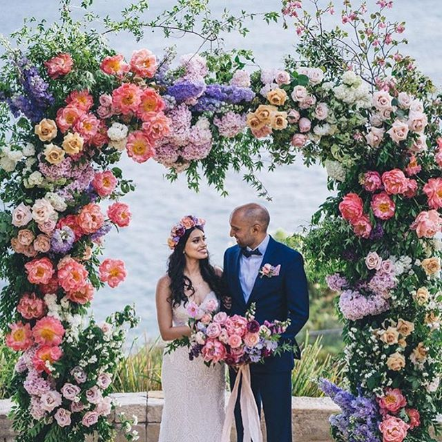 Spring ~ when we created this lush floral filled arbour of dreams for Madi & Dylan! | Myself and my team of 3 florists worked with the most beautiful fresh ingredients of the season, with love & excitement in our hearts, to bring this bespoke design to life within the short bump in time at the breathtaking @sergeantsmess ceremony space overlooking the ocean on a sunny spring afternoon! After the ceremony, we carried this (extremely heavy!) arch structure on our shoulders up the flights of stairs & inside the reception venue to re-purpose this floral feature behind the bridal table... We always love to re-purpose ceremony florals whenever time & location permits, and always go above & beyond to make our clients happy! 💗 | Madi & Dylan's wedding day was captured to perfection by @msannmarieyuen