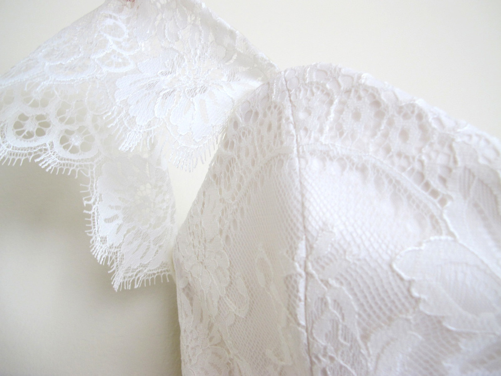 detail of lace bodice with lace flutter sleeve