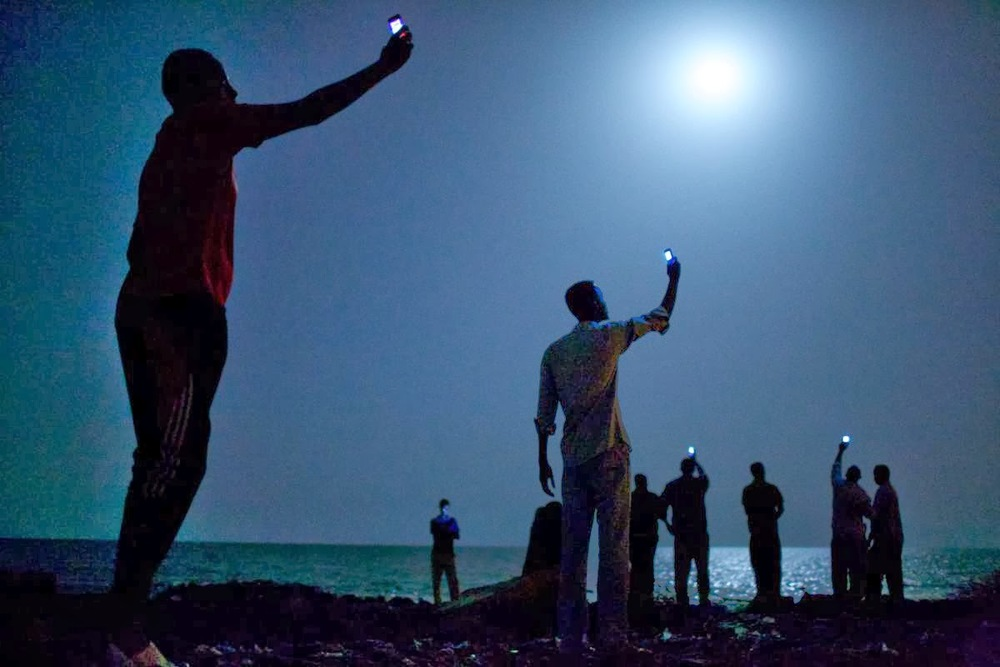 African migrants on the shore of Djibouti City at night raise their phones in an attempt to catch an inexpensive signal from neighbouring Somalia — a tenuous link to relatives abroad. (Credit: Jon Stanmeyer / VII).