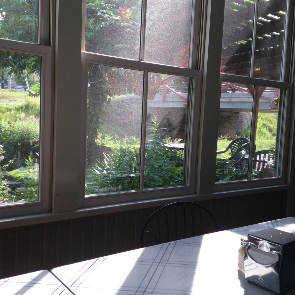 View of the canal and outside porch from the glassed-in porch.