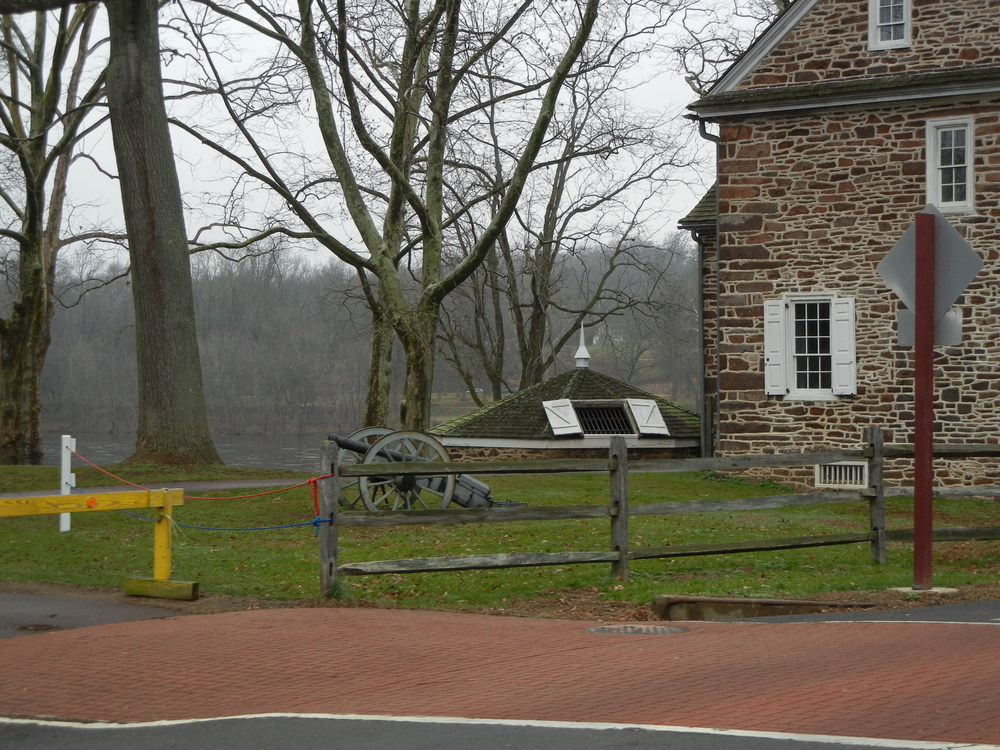 A posted cannon along with periodic housing. The open doors are a refridgerator of sorts during Colonial times.