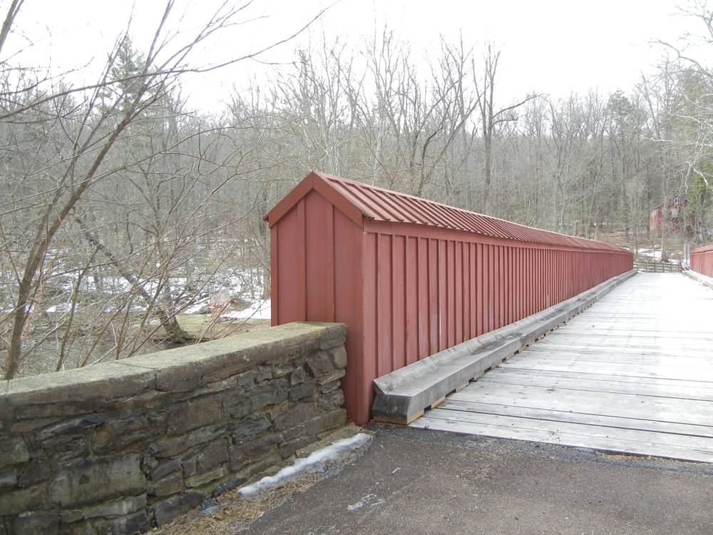 Now a footbridge, this span that connects High Rocks to Ralph Stover used to service motor cars. Cross the bridge and make a left, walk a ways down the bank of the Tohickon Creek, and one will find one of the suspected Doan Outlaws caves.