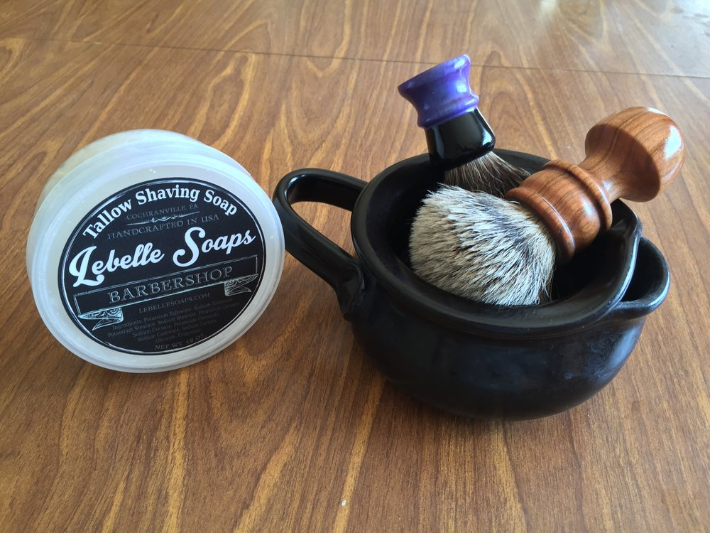 An example of a Pottersong shave scuttle with two types of brushes: the long handled Fretzwerks turned silvertip badger brush, and a facial lathering short handle brush in the back. Featured in the photo is a good starter pack for wet shaving.