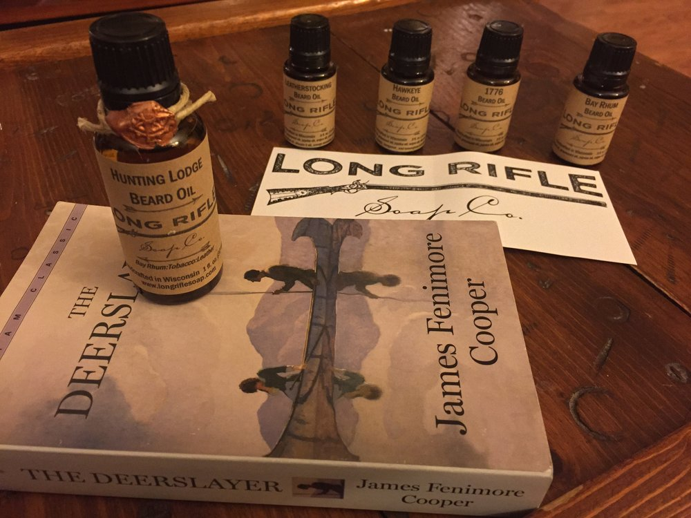 Five of the beard oils made by Long Rifle Soap Company are featured here. The Hunting Lodge vial is the full-sized product; the Leatherstocking, Hawkeye, 1776, and Bay Rhum are sample sized.
