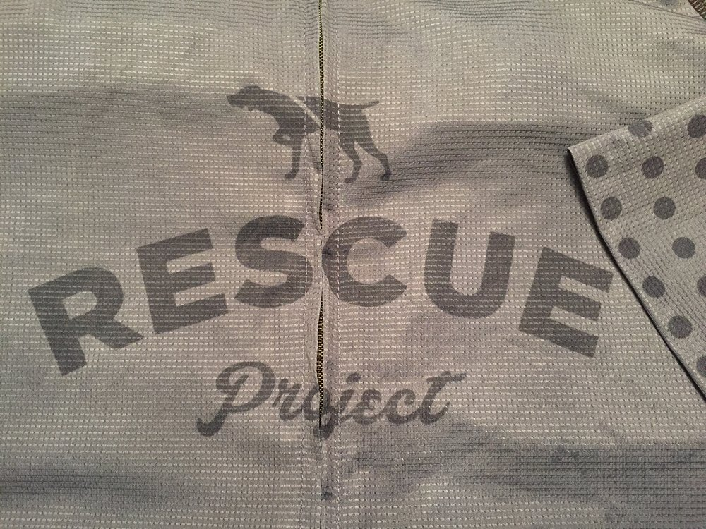 The Rescue Project logo represented on the front along with a detail of the polka dot patter on the left sleeve.