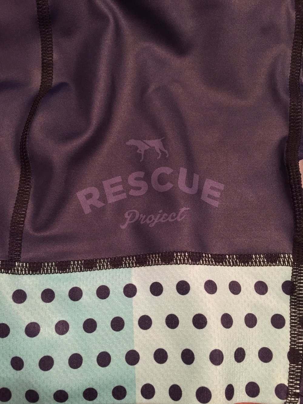 The Rescue Project logo on the left leg and detail of the celeste polka dot panel. The flip side of the left leg features a copper panel also with polka dots.