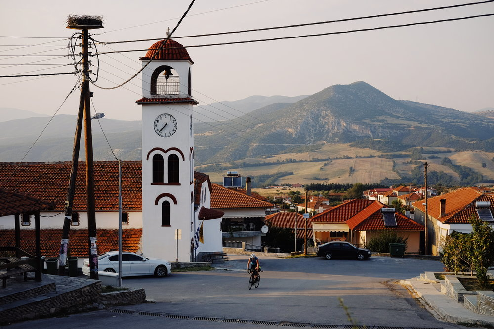 white-clock-tower-red-tile-roofs-cyclist-blue-shirt-transcontinental06