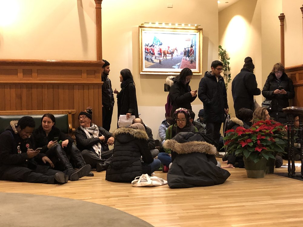 Community members conduct impromptu sit after being blocked from entering city hall and Mayor Toni Harp's office by New Haven Police.