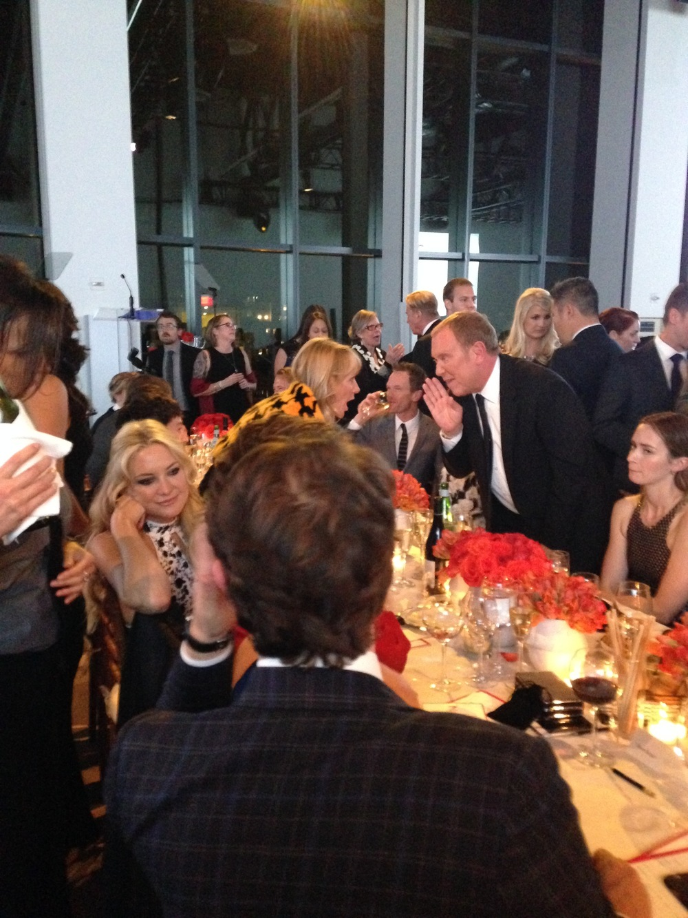 Kate Hudson casually chatting with someone as Emily Blunt looks on. NPH drinking his glass of wine, as Michael Kors chats up with a guest.