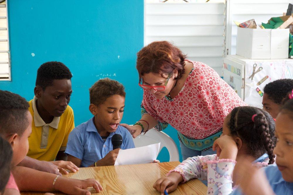 Rita Rosa Ruesga and public school students reading out loud rhymes.
