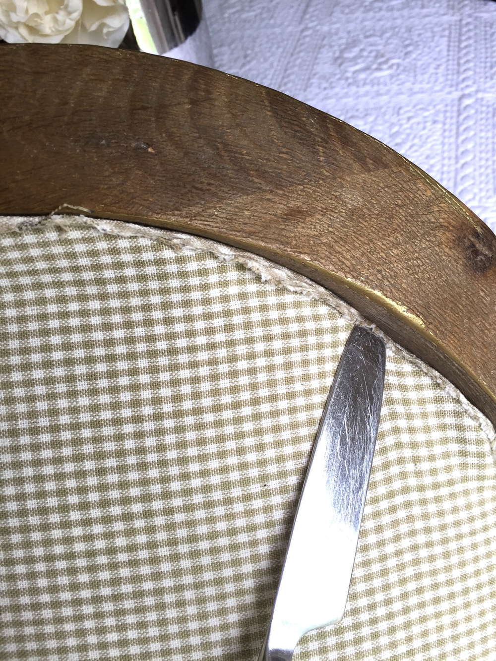 using a butter knife, tuck fabric into frame.