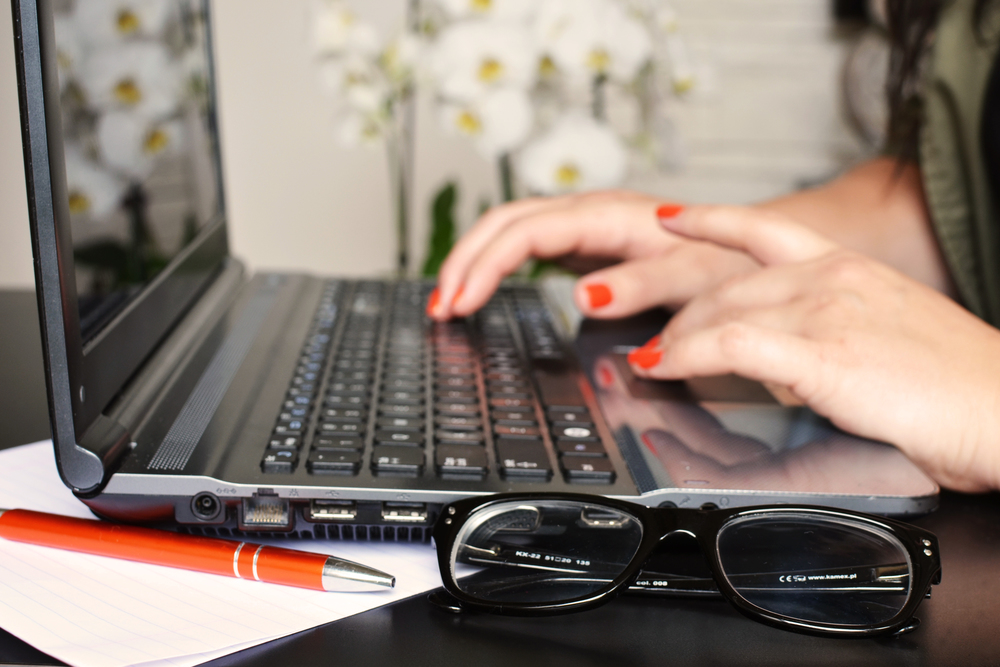 woman with painted nails typing on a laptop