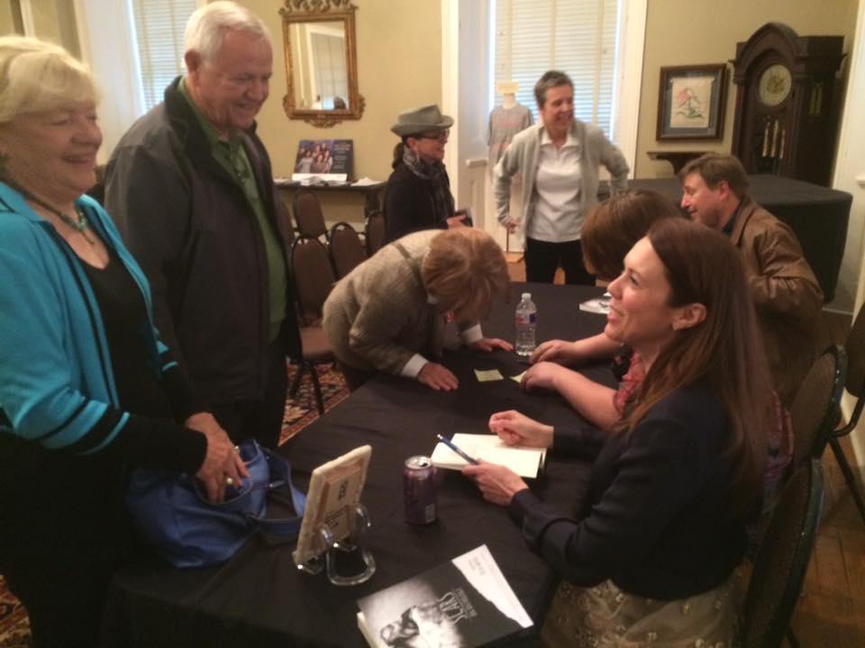 Erin Wood signs a copy of Scars for former Congressman Ed Bethune and his wife, Lana, during the Scars panel at the MacArthur Museum of Arkansas Military History during the 2016 Arkansas Literary Festival. Photo courtesy panel mediator Michael Hibblin of KUAR radio.