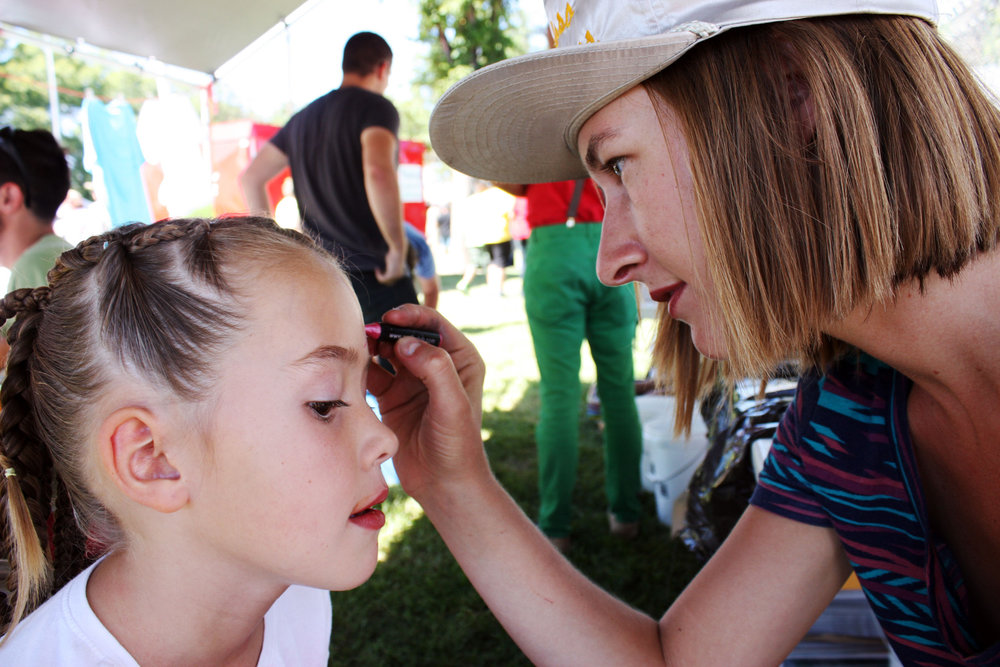 Erica Dixon face-painting at Epicenter's kids arts booth at Melon Days.