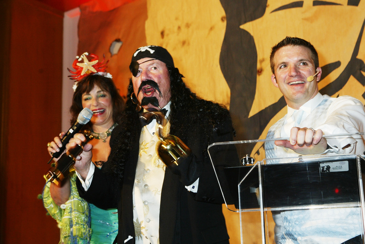 Why is Greg onstage with a pirate and a woman with a crab for a crown? And why is the crowd bidding like mad on their auction lot? Chuck Huggins, CEO of Sees Candy for 54 years, was always a celebrity to those who knew him.
